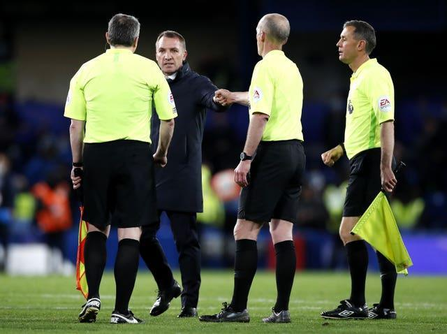 Brendan Rodgers, second left, speaks to the match officials after the game