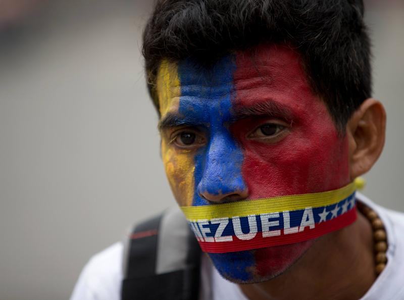A man wears a narrow strip in the colors of Venezuela's flag over his mouth in protest of officials breaking up camps maintained by student protesters, in Caracas, Venezuela, Thursday, May 8, 2014. Hundreds of security forces broke up four camps maintained by student protesters, arresting more than 200 people in a pre-dawn raid. The camps of small tents were installed more than a month ago in front of the UN building and other anti-government strongholds in the capital to protest against President Nicolas Maduro's government. (AP Photo/Fernando Llano)