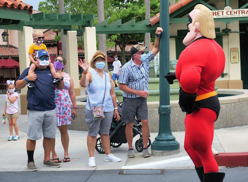 Guests wave to Mr. Incredible during a pop-up appearance of Pixar characters at Disney's Hollywood Studios at Walt Disney World on July 16, the second day of the park's reopening, in Lake Buena Vista, Florida. (Photo: Orlando Sentinel via Getty Images)