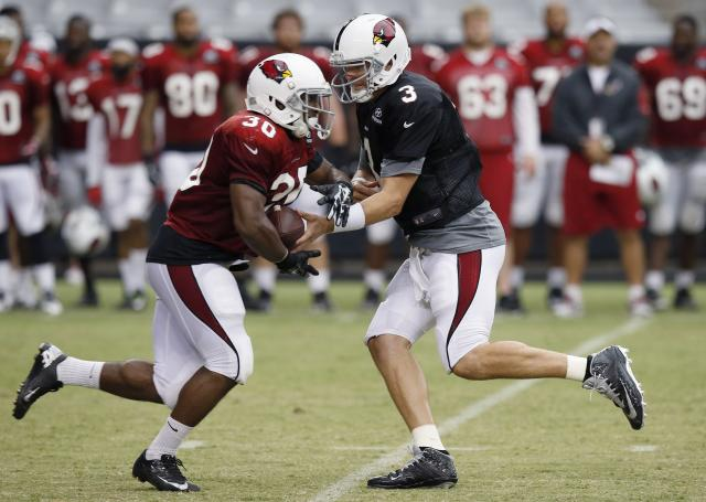 Arizona Cardinals' Carson Palmer (3) hands the ball off to Stepfan Taylor (30) during NFL football training camp practice on Wednesday, July 30, 2014, in Glendale, Ariz. (AP Photo/Ross D. Franklin)