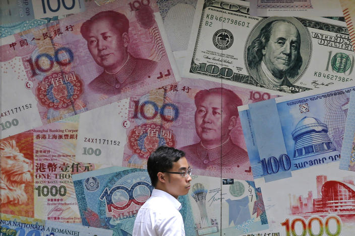 FILE - In this June 10, 2019, file photo, a man walks past a money exchange shop decorated with different banknotes at Central, a business district of Hong Kong. China's yuan fell below the politically sensitive level of seven to the U.S. dollar on Monday, Aug. 5, 2019, possibly adding to trade tension with Washington. The currency weakened to 7.0177 in early trading following U.S. President Donald Trump's threat last week of tariff hikes on additional Chinese imports in a fight over Beijing's trade surplus and technology policies. (AP Photo/Kin Cheung, File)