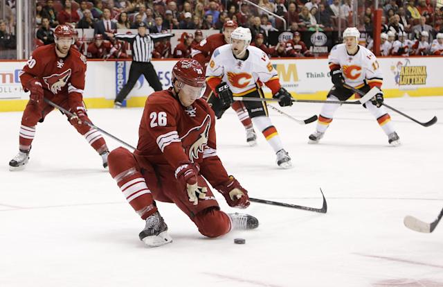 Phoenix Coyotes' Michael Stone (26) stops a pass as Calgary Flames' Ben Hanowski (58) and Lance Bouma (17) look on during the first period of an NHL hockey game on Saturday, March 15, 2014, in Glendale, Ariz. Coyotes' Chris Summers watches the action. (AP Photo/Matt York)
