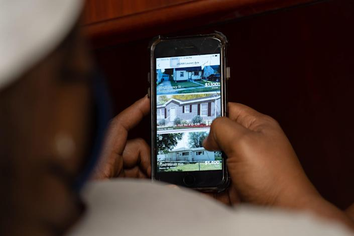 Quantanique Anderson of Detroit looks through housing listings while working with Macomb County Rotating Emergency Shelter Team (MCREST) case manager Kristin Lawrence to search for affordable housing through their program in Macomb County on July 26, 2021 at the MCREST building in Roseville.
