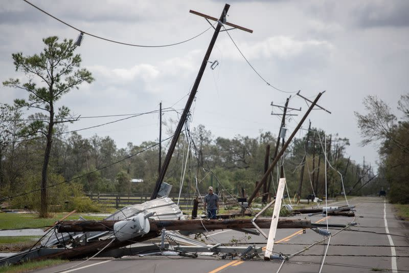 Man walks past fallen electrical lines to get to residence in aftermath of Hurricane Laura in Sulphur, Louisiana