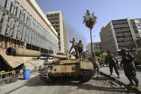 Members of the Libyan pro-government forces, backed by locals, gather on a tank outside the Central Bank, near Benghazi port