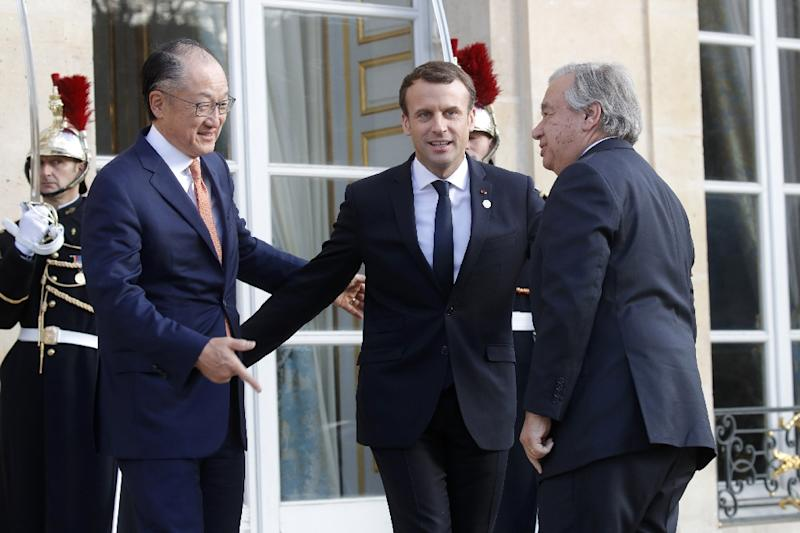 French President Emmanuel Macron (C) welcomes World Bank President Jim Yong Kim (L) and UN Secretary General Antonio Guterres before their meeting at the Elysee Palace in Paris as part of the One Planet Summit on December 12, 2017 (AFP Photo/Philippe WOJAZER)