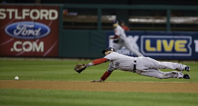 Boston Red Sox second baseman Dustin Pedroia dives for a double by St. Louis Cardinals second baseman Matt Carpenter during the third inning of Game 4 of baseball's World Series Sunday, Oct. 27, 2013, in St. Louis. (AP Photo/Matt Slocum)