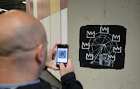 A man takes a photo of one of two new murals painted by the artist Banksy near the Barbican Centre in London. The works mark the opening of an exhibition by American artist Jean-Michel Basquiat at the arts venue.