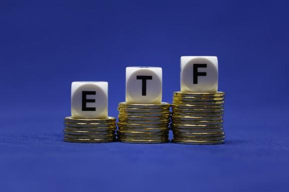 Three piles of coins with letter-cubes spelling ETF on top of them, on a blue background.