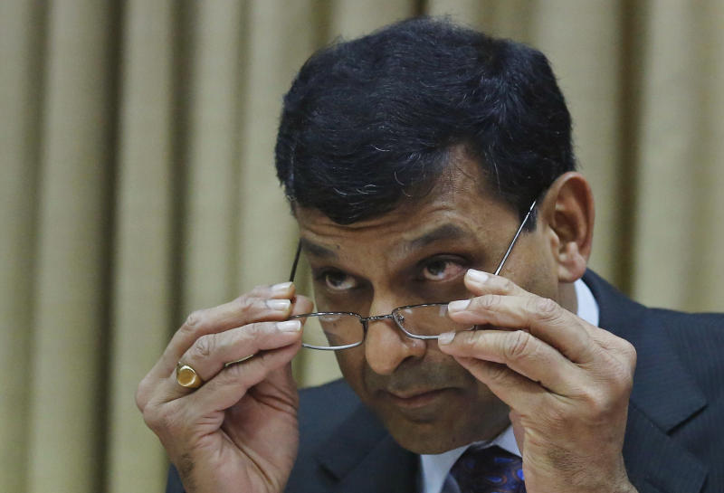 Reserve Bank of India (RBI) Governor Raghuram Rajan adjusts his glasses as he attends the second quarter review of monetary policy for 2013-14 at the RBI headquarters in Mumbai, India, Tuesday, Oct 29, 2013. India's central bank raised its key interest rate for the second time in two months, underlining its determination to control inflation despite concerns economic growth could slow further.(AP Photo/Rafiq Maqbool)