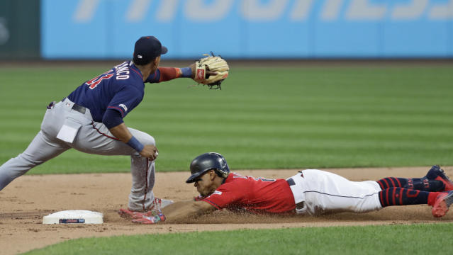 Cleveland Indians' Francisco Lindor, right, slides safely into second base for a double as Minnesota Twins' Jorge Polanco waits for the ball in the first inning in a baseball game Friday, Sept. 13, 2019, in Cleveland. (AP Photo/Tony Dejak)