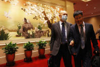 Deng Ming, deputy director of China's National Narcotics Control Commission, second from right walks out with another man after attending a press conference in Beijing on Tuesday, May 11, 2021. China on Tuesday said it will add all synthetic cannabinoids to its list of banned drugs, in what it described as a first in the world, to curb their manufacturing, trafficking and abuse. (AP Photo/Ng Han Guan)