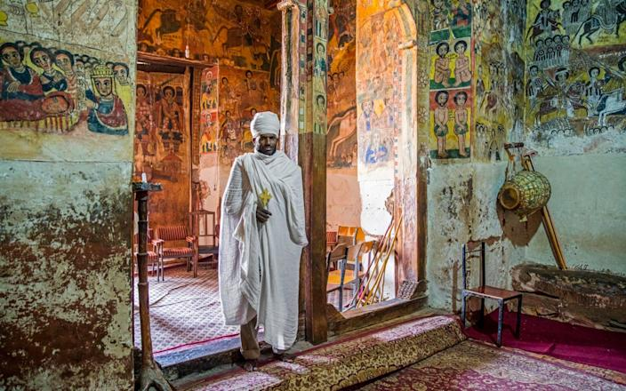 Orthodox priest inside Abreha We Atsbeha rock-hewn church decorated with medieval wall paintings near Wukro, Misraqawi Zone, Tigray Region - Arterra/Marica van der Meer/Universal Images Group via Getty Image