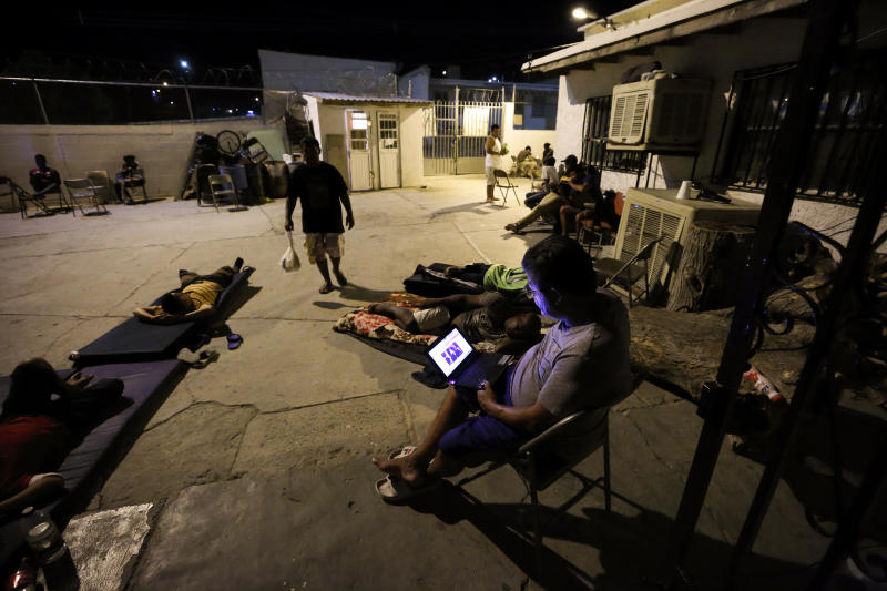 In this July 25, 2019, photo, a Cuban man looks at a computer screen as others lay around the patio at El Buen Pastor shelter for migrants in Cuidad Juarez, Mexico. (AP Photo/Gregory Bull)