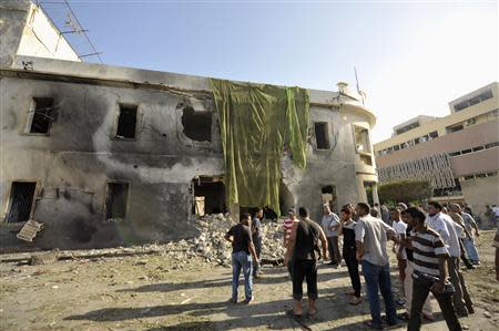 People look at the site of an explosion at a Libyan Foreign Ministry building in Benghazi