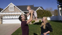 FILE - Matthew Clewett, 26, play with his daughter Nellie, while his wife Bethany looks on at their home Thursday, April 29, 2021, in Kaysville, Utah. Utah is one of two Western states known for rugged landscapes and wide-open spaces that are bucking the trend of sluggish U.S. population growth. The Clewett's want to have a large family like the ones they grew up in, but high housing costs could put a serious damper on that plan. The couple bid on at least 10 houses in northern Utah before they could close on a starter home for themselves and their infant daughter. (AP Photo/Rick Bowmer)
