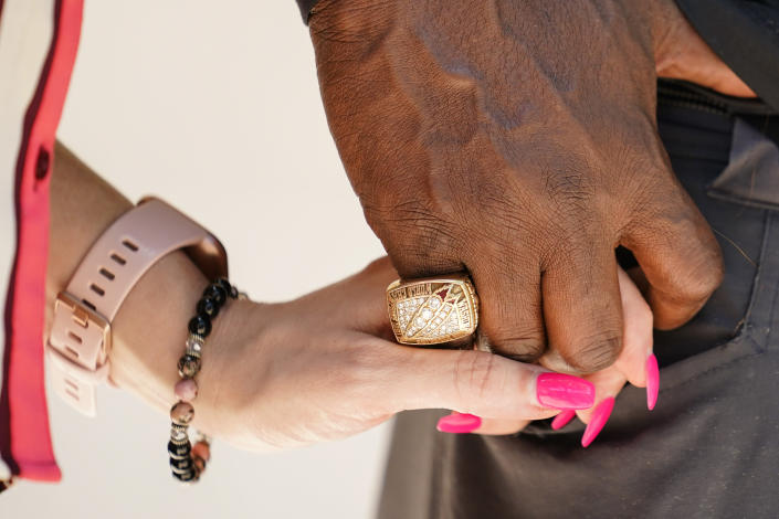 """Former NFL player Clarence Vaughn III and his wife Brooke Vaughn hold hands before delivering thousands of petitions demanding equal treatment for everyone involved in the settlement of concussion claims against the NFL, to the federal courthouse in Philadelphia, Friday, May 14, 2021. Thousands of retired Black professional football players, their families and supporters are demanding an end to the controversial use of """"race-norming"""" to determine which players are eligible for payouts in the NFL's $1 billion settlement of brain injury claims, a system experts say is discriminatory. (AP Photo/Matt Rourke)"""