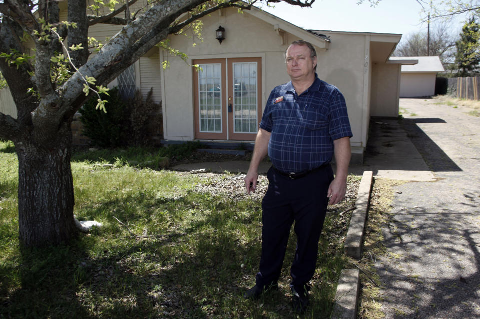 Realtor Rick Cumins poses for a picture outside of a house that he's been trying to sell for six months in Cleburn, Texas March 24, 2009. Small-town Texan realtor Cumins is going to see a paycheck in April -- his first since December. REUTERS/Jessica Rinaldi (UNITED STATES BUSINESS)