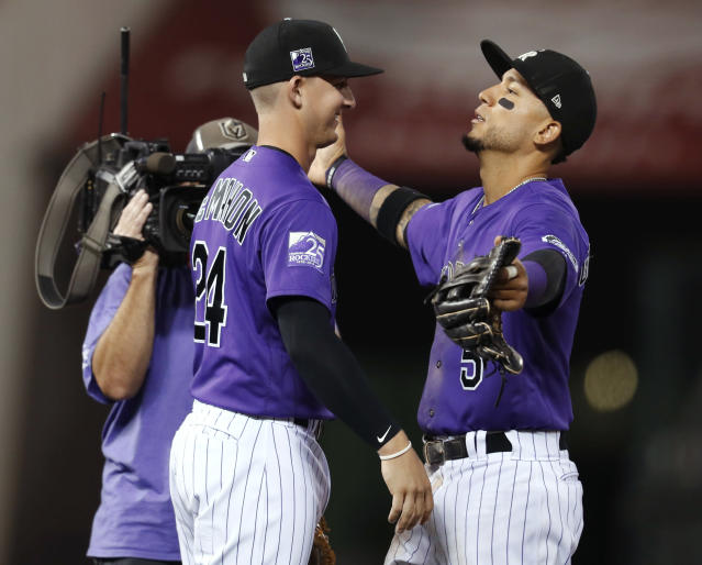 Colorado Rockies right fielder Carlos Gonzalez, right, prepares to embrace third baseman Ryan McMahon after the Rockies' 5-4 win over the Los Angeles Dodgers in a baseball game Friday, Aug. 10, 2018, in Denver. (AP Photo/David Zalubowski)