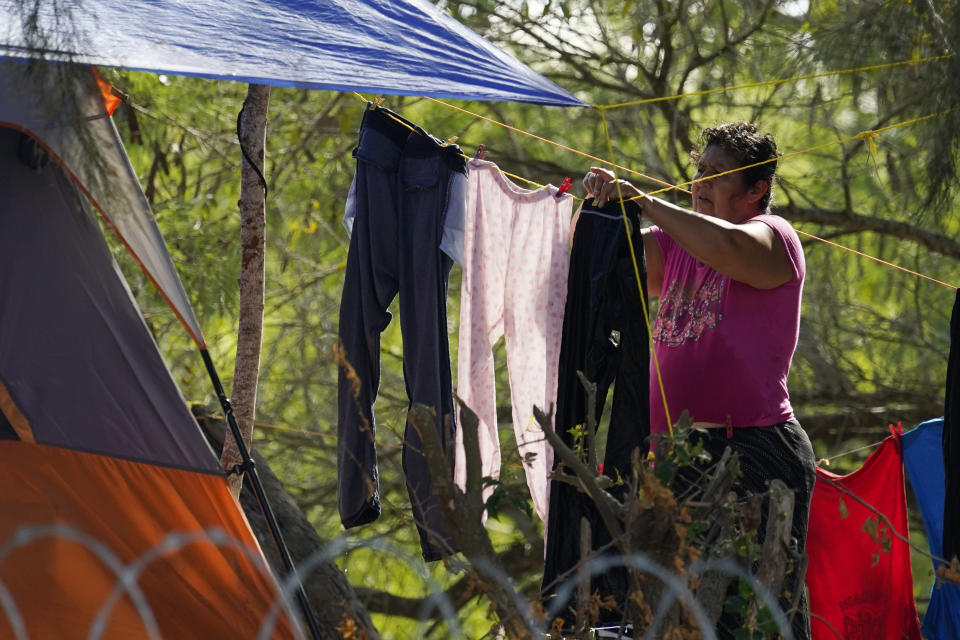 A person seeking asylum in the U.S. and waiting in Mexico, hangs laundry on a clothesline at a camp in Matamoros, Mexico, Thursday, Nov. 19, 2020. Led by U.S. military veterans, Global Response Management is staffed by volunteers primarily from the U.S. and paid asylum seekers who were medical professionals in their homelands. The group has treated thousands of migrants over the past year at two clinics in Matamoros, including one inside the camp. (AP Photo/Eric Gay)