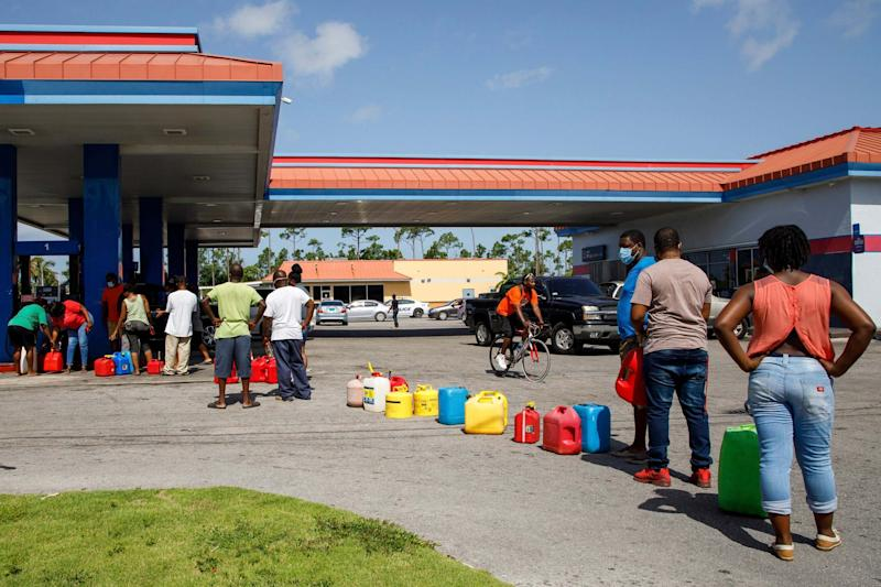 Residents wait in line to fill their containers with gasoline before the arrival of Hurricane Isaias in Freeport, Bahamas (AP)