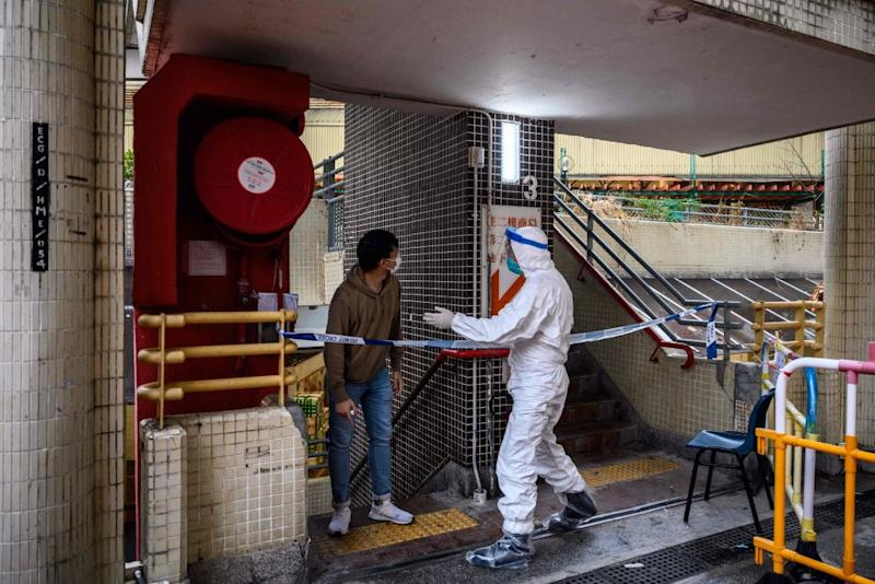 A police officer wearing protective gear instructs a resident at a Hong Kong apartment block where an outbreak of coronavirus was detected.
