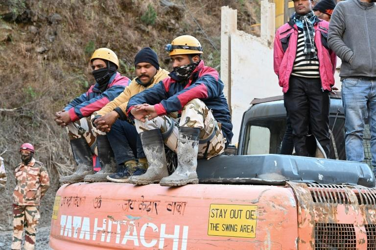 Rescue personnel rest on an excavator outside a tunnel blocked with debris during rescue operations in Tapovan of Chamoli district on February 8