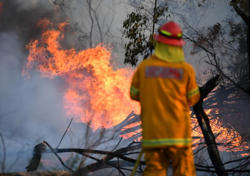 A firefighter attempting to repel flames near Torrington, in the Glen Innes region on Sunday. Source: AAP