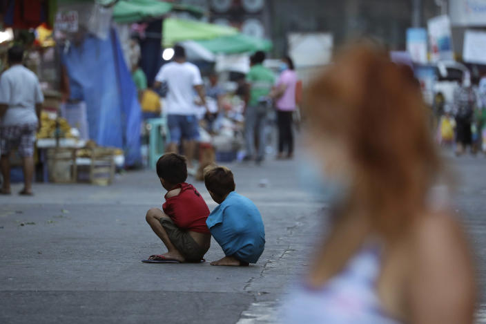 Boys use their shirts to keep warm as they sit in the middle of the street during stricter health protocols at downtown Manila, Philippines on Wednesday, March 24, 2021. The Philippines has reported more than 677,000 confirmed COVID-19 infections, with nearly 13,000 deaths, the highest totals in Southeast Asia after Indonesia. (AP Photo/Aaron Favila)