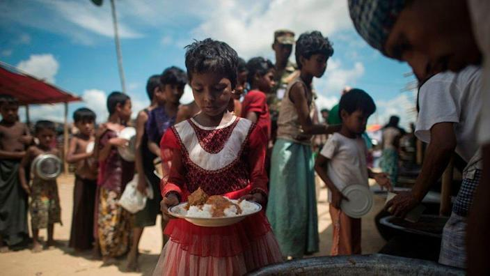 In this picture taken on October 1, 2017, Rohingya Muslim refugees line up to receive food at a distribution area at Balukhali refugee camp near the town of Gumdhum in Cox's Bazar.