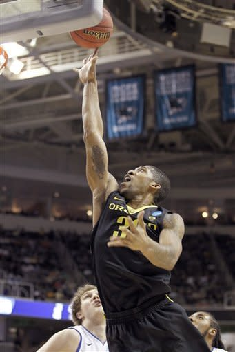 Oregon forward Carlos Emory (33) takes a shot past Saint Louis forward Rob Loe (51) during the first half of a third-round game in the NCAA college basketball tournament Saturday, March 23, 2013, in San Jose, Calif. (AP Photo/Tony Avelar)