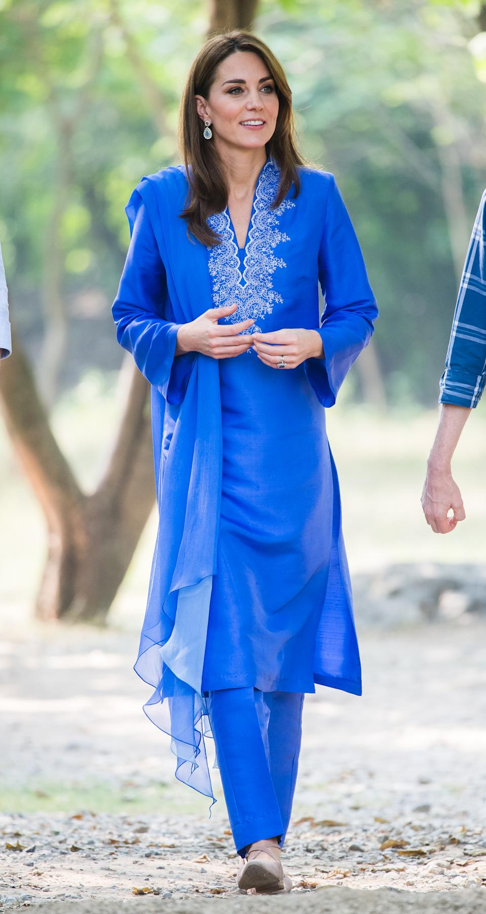 """Kate wore a traditional, royal blue shalwar kameez by Pakistani designer Maheen Khan for her first official occasion on the tour. A pair of <a href=""""https://fave.co/2Mj8bXq"""" rel=""""nofollow noopener"""" target=""""_blank"""" data-ylk=""""slk:£24 shoes from New Look"""" class=""""link rapid-noclick-resp""""><strong>£24 shoes from New Look</strong></a> completed the outfit. The Duchess then changed into a pair of <a href=""""https://fave.co/2MMzGHY"""" rel=""""nofollow noopener"""" target=""""_blank"""" data-ylk=""""slk:Russell & Bromley flats, costing £195"""" class=""""link rapid-noclick-resp""""><strong>Russell & Bromley flats, costing £195</strong></a>. <em>[Photo: Samir Hussein/WireImage]</em>"""