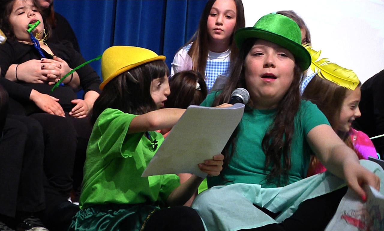 """In this Feb. 4, 2012 image made from video, 9-year-old Clara Beatty helps Zuzu Smith with her lines during a play in Winnetka, Ill. Clara is a """"buddy mentor"""" for the Special Gifts Theatre, a drama troupe for children with special needs. Her mother, Janet, says at home or school or church, there, people know her. To them, she is just Clara - the funny, kind girl who wants to be a doctor when she grows up, who's quick to help classmates with homework when she finishes her own. (AP Photo/Martha Irvine)"""