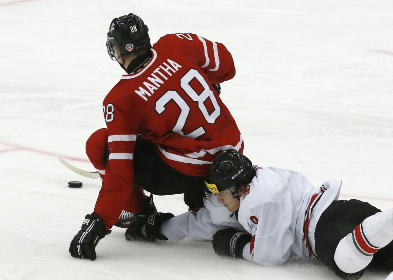 Canada's Anthony Mantha (L) is hauled down on a break-away by Switzerland's Samuel Kreis during the second period of their IIHF World Junior Championship ice hockey game in Malmo, Sweden, January 2, 2014. Matha was awarded a penalty shot. REUTERS/Alexander Demianchuk (SWEDEN - Tags: SPORT ICE HOCKEY)