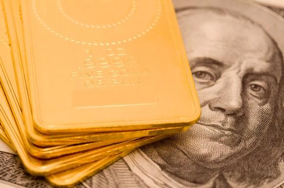 A stack of gold ingots lying atop a hundred dollar bill.