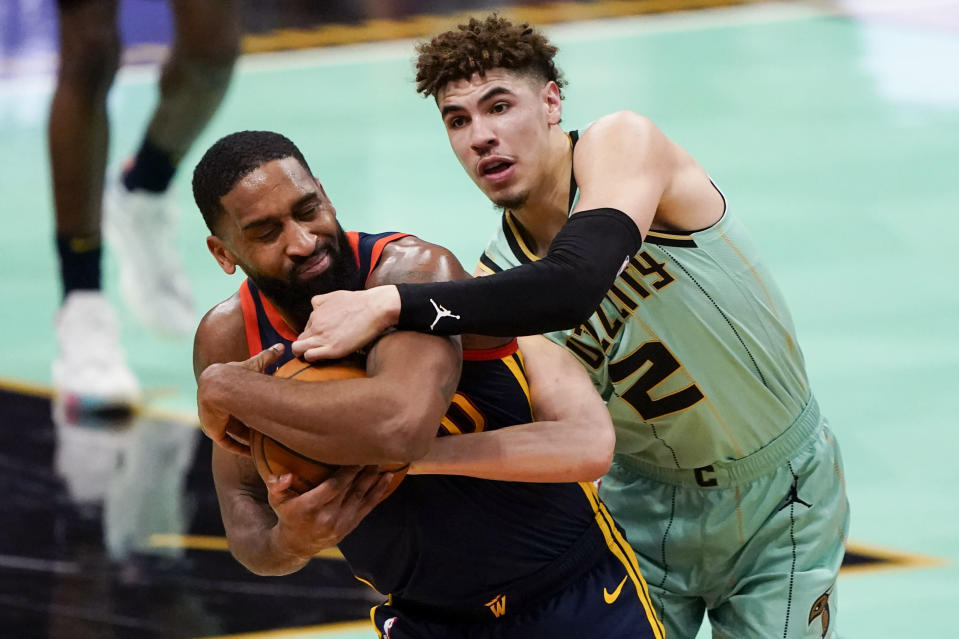 Golden State Warriors guard Brad Wanamaker, left, and Charlotte Hornets guard LaMelo Ball battle for the ball during the second half of an NBA basketball game on Saturday, Feb. 20, 2021, in Charlotte, N.C. (AP Photo/Chris Carlson)