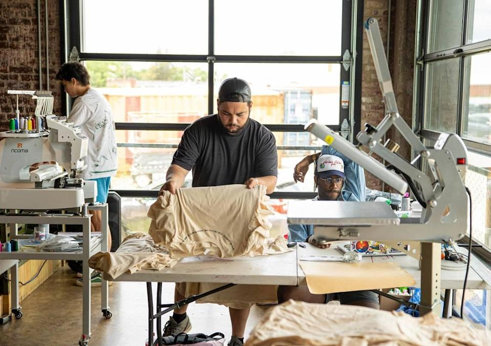 Mason Thomas, left, Anthony Colón, center, and Hasam Dirton work on their projects at MacFly Printing Co. at Camp North End in Charlotte, on Wednesday, June 9, 2021. U.S. Senate hopeful Cheri Beasley stopped by as she campaigned in Charlotte.