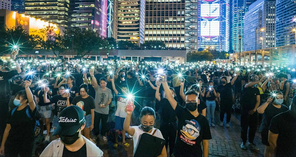 Secondary school students raise their phone torches as they sing 'Do You Hear the People Sing' from 'Les Miserables' while attending a rally at Edinburgh Place in Hong Kong on August 22, 2019. - Hong Kong student leaders on Thursday announced a two-week boycott of lectures from the upcoming start of term, as they seek to keep protesters on the streets and pressure on the government. (Photo by Anthony WALLACE / AFP) (Photo credit should read ANTHONY WALLACE/AFP/Getty Images)