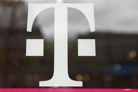 A T-Mobile logo is seen on the storefront door of a store in Manhattan, New York, U.S., April 30, 2018. REUTERS/Shannon Stapleton/File Photo