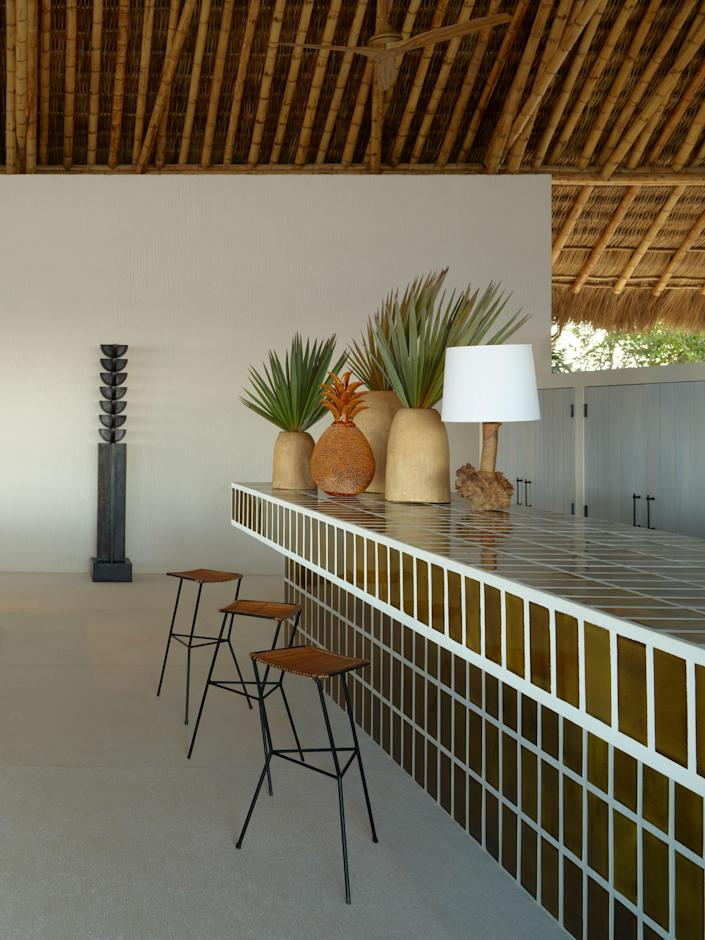 Vintage stools pull up to a Cerámica Suro tile-lined bar. Steel sculpture by Rufino Tamayo.