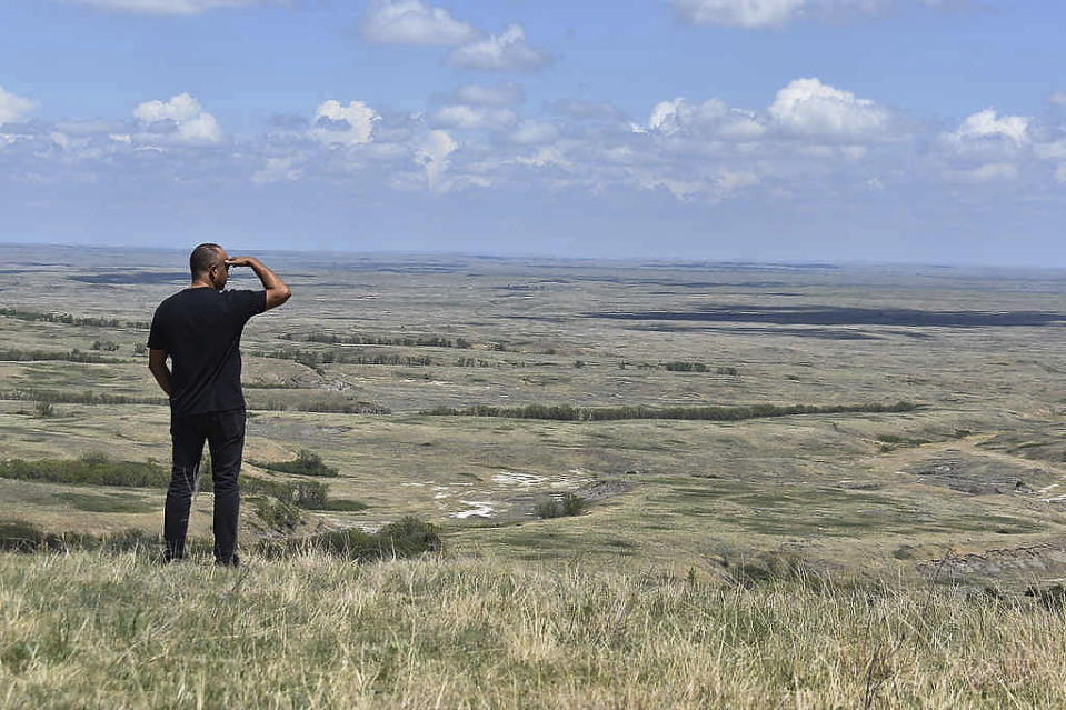 """In this Thursday, May 20, 2021, photo, Joseph McNeil Jr., manager of Standing Rock's energy authority, looks over the site of the proposed 235-megawatt Anpetu Wi, or """"Morning Light,"""" Wind Farm in the Porcupine Hills on the Standing Rock Sioux Reservation near Fort Yates, N.D. Officials predict its 235 megawatts, enough for roughly 94,000 homes, would double their annual revenue and fund benefits like those Fort Berthold derives from oil, such as housing, health care and more jobs. (AP Photo/Matthew Brown)"""