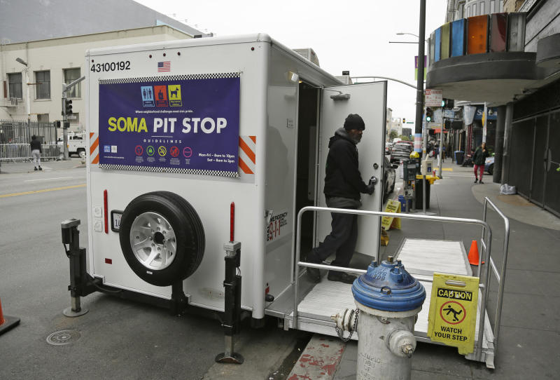 """An attendant exits a """"Pit Stop"""" public toilet on Sixth Street, Thursday, Aug. 1, 2019, in San Francisco. A 5-year-old portable toilet program in San Francisco that provides homeless people with a private place to go has expanded to 25 locations in the city and has spread to Los Angeles. Not everyone who uses the """"Pit Stop"""" toilets is homeless, but advocates say steam cleaning requests have dropped in surrounding areas. (AP Photo/Eric Risberg)"""