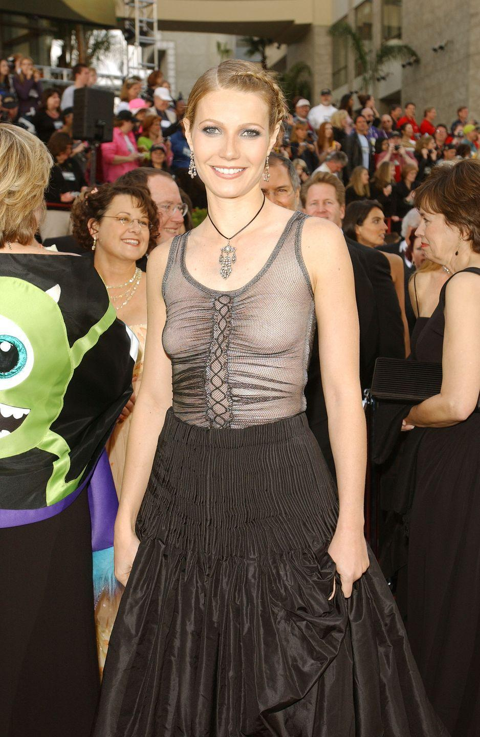 """<p>Gwyneth herself expressed some regrets about this red carpet look. In a <a href=""""https://www.today.com/style/gwyneth-paltrow-i-should-have-worn-bra-2002-oscars-1C8637763"""" rel=""""nofollow noopener"""" target=""""_blank"""" data-ylk=""""slk:post for Goop"""" class=""""link rapid-noclick-resp"""">post for Goop</a> several years later, she said, """"I still love the dress itself but I should have worn a bra."""" She may have loved the dress, but critics didn't. One <em>Guardian </em>writer wrote, """"The usually chic Gwyneth Paltrow came a cropper in a tacky transparent black vest by Alexander McQueen. Her gap-year plaits, goth eye make-up and clunky jewellery were more Camden Market than red carpet.""""  </p>"""