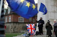 An anti-Brexit activist waves an EU flag and a Union Jack flag as he demonstrates opposite the Houses of Parliament in central London on January 9, 2019