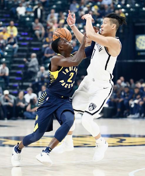 Darren Collison (L) of the Indiana Pacers and Jeremy Lin of the Brooklyn Nets fight for a loose ball at Bankers Life Fieldhouse in Indianapolis, Indiana, on October 18, 2017
