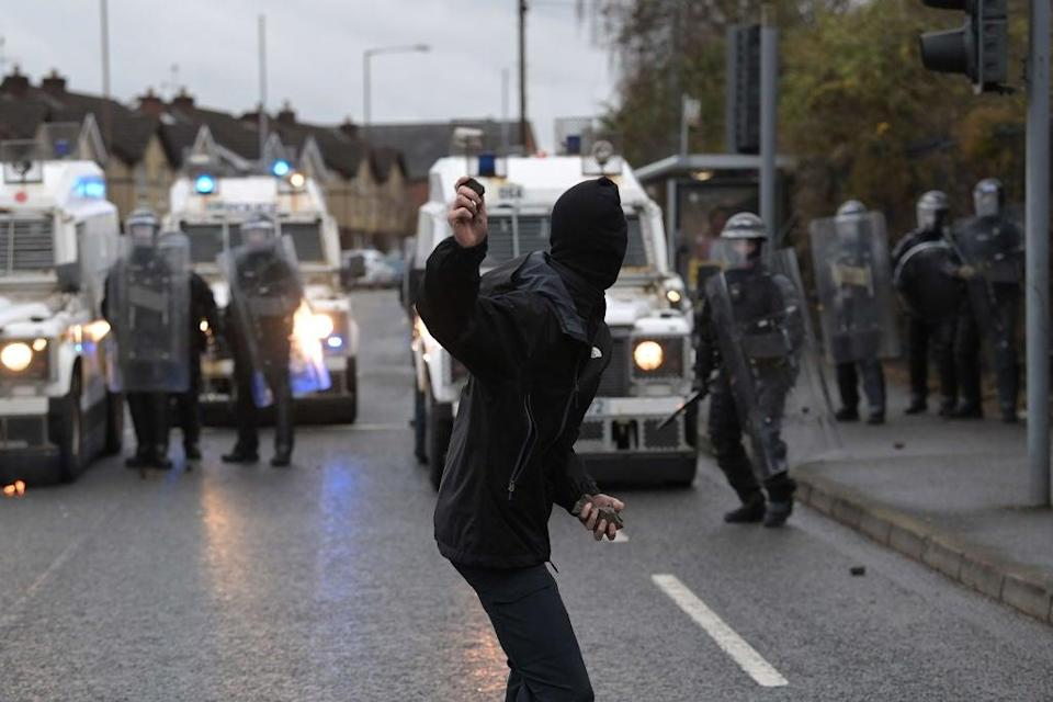 <p>A nationalist attacks police on Springfield Road, near the Peace Wall gates dividing nationalist and loyalist communities, on 8 April</p> (Getty Images)