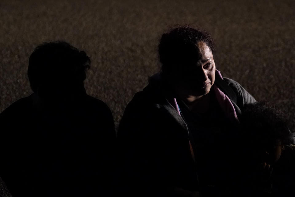 A migrant from Honduras sits in line with others after turning herself in upon crossing the U.S.-Mexico border Monday, May 17, 2021, in La Joya, Texas. The Biden administration has agreed to let up to about 250 people a day in the United States at border crossings with Mexico to seek refuge, part of negotiations to settle a lawsuit over pandemic-related powers that deny migrants a right to apply for asylum, an attorney said Monday. (AP Photo/Gregory Bull)
