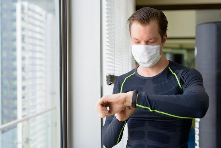 Man wearing a face mask checks his heart rate using his smart watch.