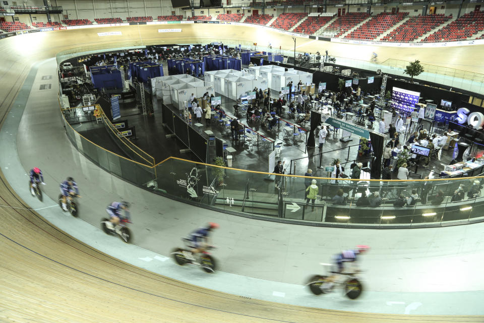 Riders train at the National Velodrome at Saint-Quentin-en-Yvelines, west of Paris, Saturday, March 27, 2021, that has been transformed into a mass vaccination center. Saturday marked the first day in France of vaccination for healthy people aged 70 and above. (AP Photo/John Leicester)
