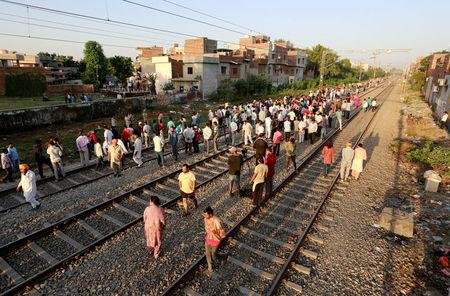 People gather at the site of an accident after a commuter train traveling at high speed ran through a crowd of people on the rail tracks in Amritsar
